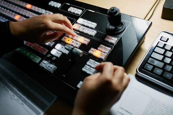 Student using control panel in broadcast studio