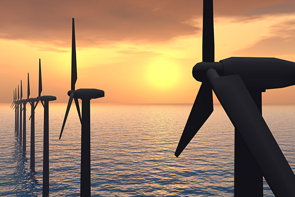 A row of wind turbines in the sea, in front of a sunset