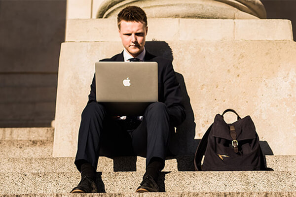 Byron sits on Portsmouth Guildhall steps, working on a laptop