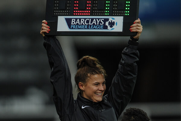 Lucy holds up a substitution board at a football match