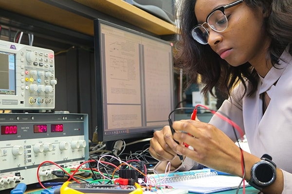 Savannah Pascall working on electronic circuit board in laboratory