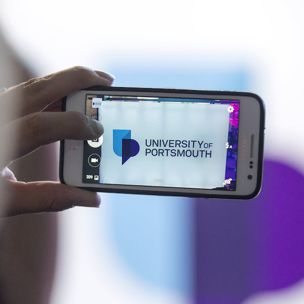 person on phone taking picture of UoP logo