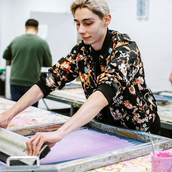 A student rolling out paint on fabric printing base