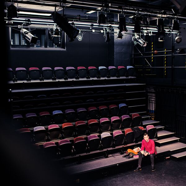 A student sitting below many rows of coloured seats in a dark spotlit drama studio