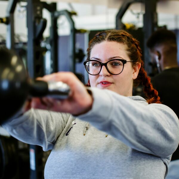 Female using kettlebell in University gym