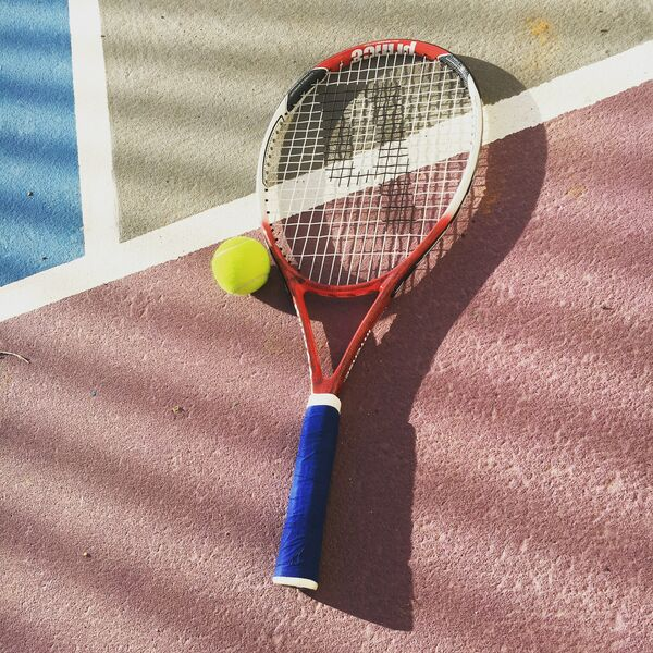tennis racket and tennis ball on tennis court