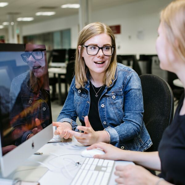 two female students talking in front of a Apple computer