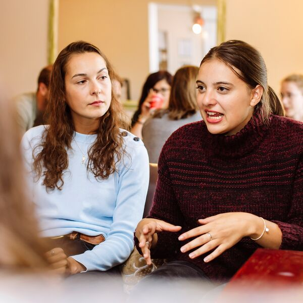 Two female students talking in a group