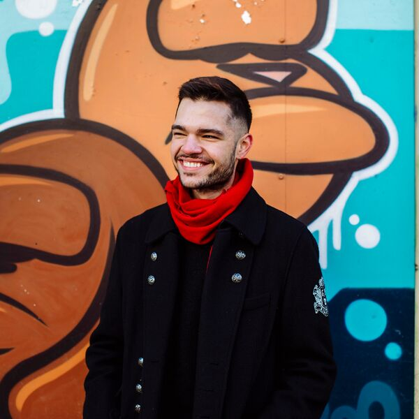 Male student stood smiling in front of an artistic wall