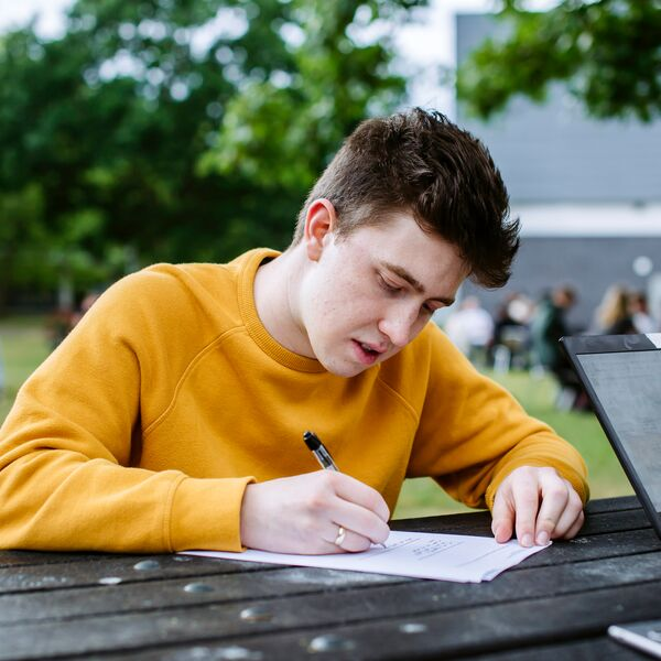 Male student in yellow jumper studying outside