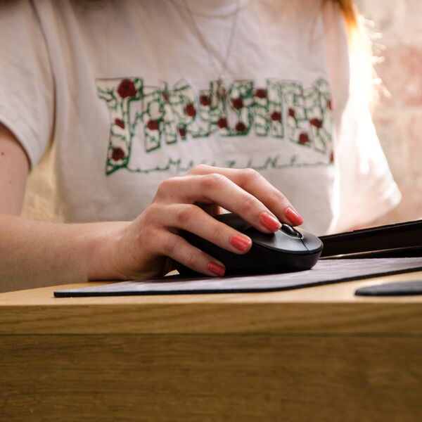 Person wearing red nail varnish using computer mouse