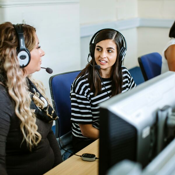 Students wearing headsets at computers in language labs