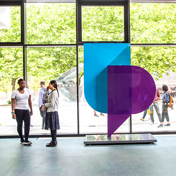 Students standing by the University of Portsmouth logo sculpture in Dennis Sciama Building