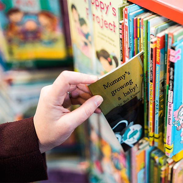 Teacher's hand extracting early years book from shelf