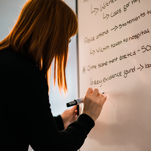 Woman writing crime studies notes on white board