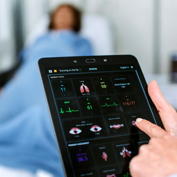 Medical professional using a tablet to monitor health in a hospital ward