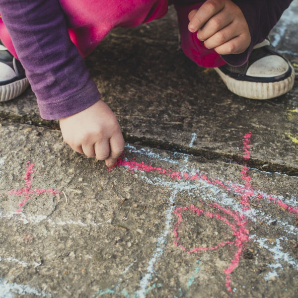 child drawing with chalk on pavement