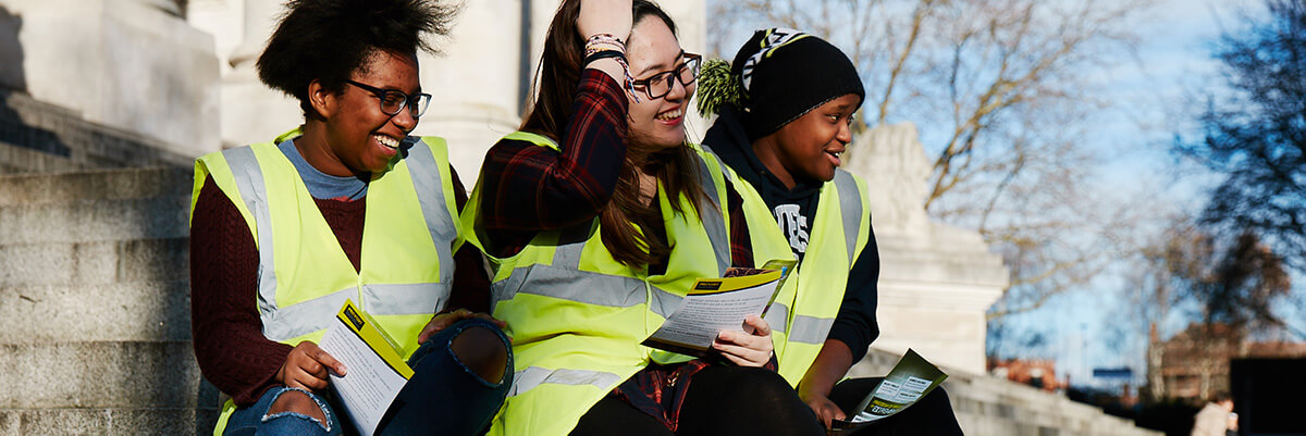 Group of female students smiling in yellow vests in front of Guildhall