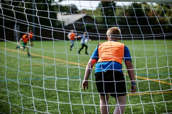 Male goalkeeper in orange vest watches pitch