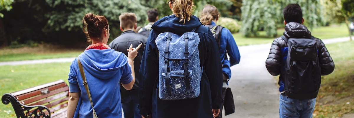 University of Portsmouth students carrying backpacks through the park