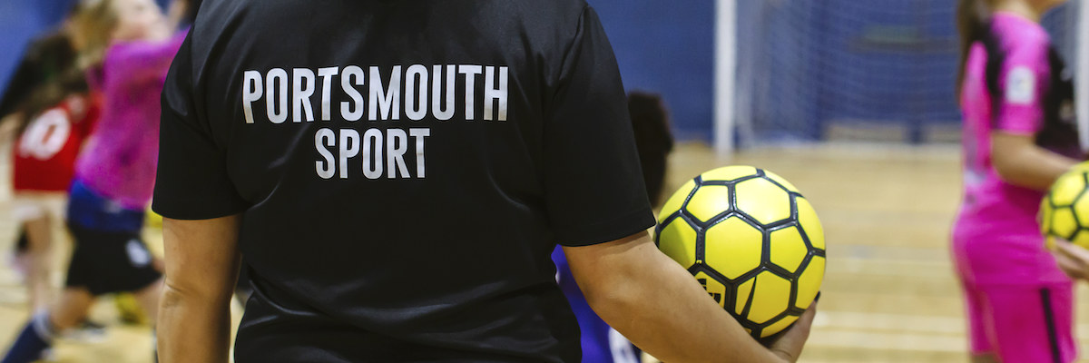 University of Portsmouth Sport staff member holding a football