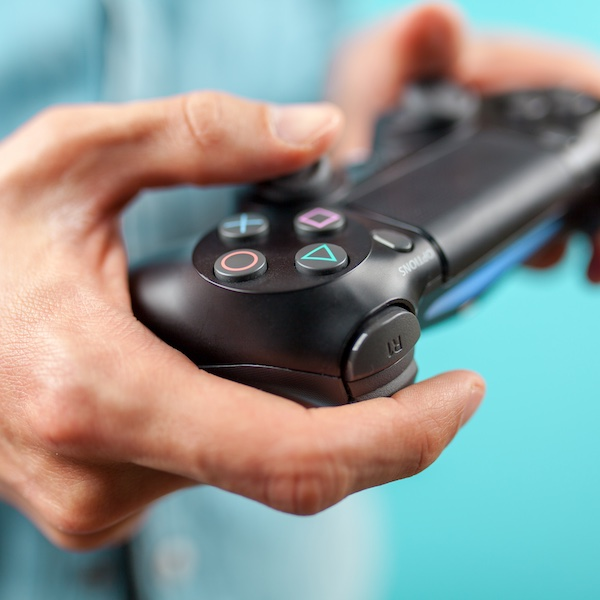 Male gamer holding playstation controller