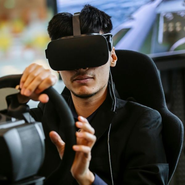 Male research participant driving car in VR headset