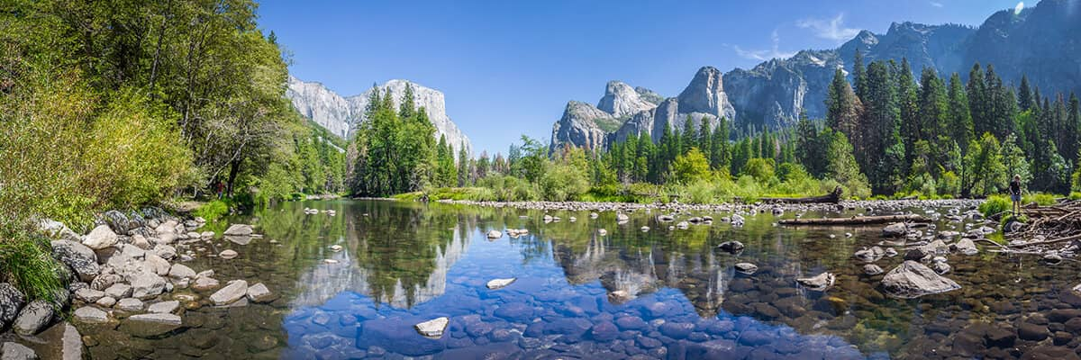 clear water river with trees and mountains in background