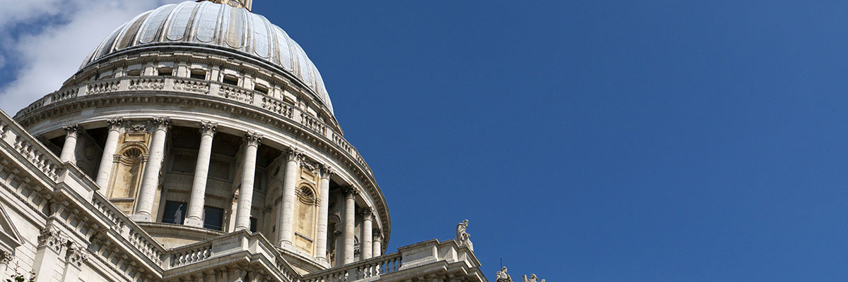 Dome of the Royal Courts of Justice against a deep blue sky with a few clouds