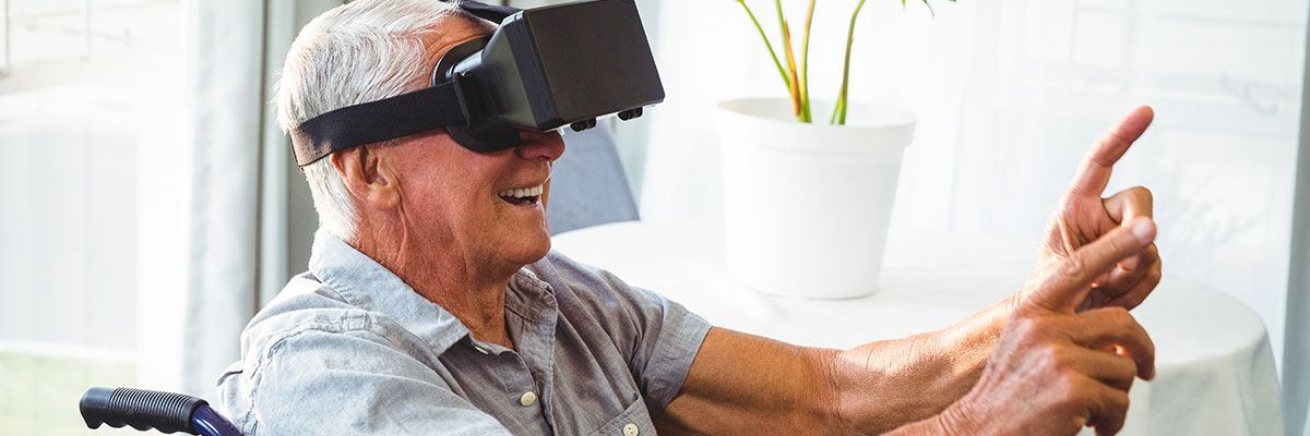 Smiling elderly man sits in a chair wearing virtual reality goggles holding up his hands