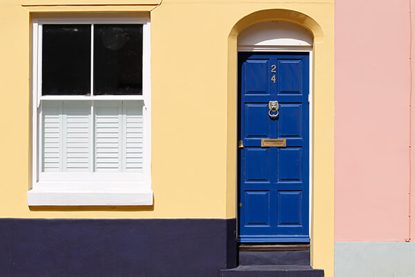 The red and yellow fascia of a terraced house, with a blue door