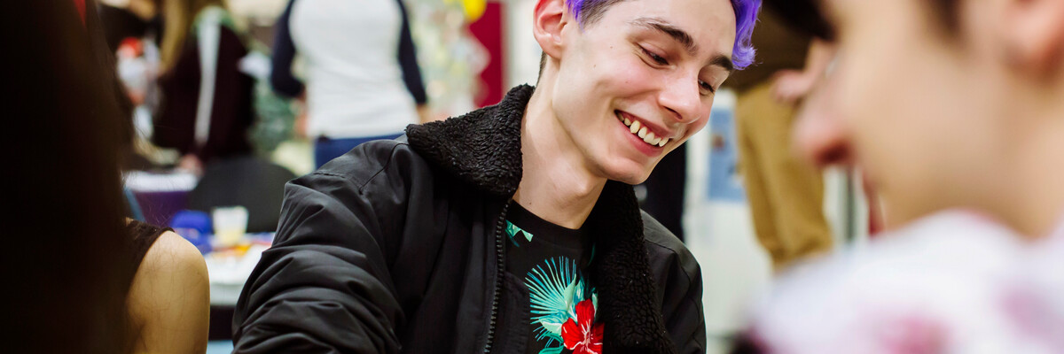 Student with purple hair smiles with friends at the feel good festival