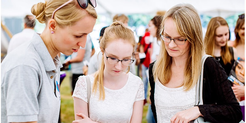 A University guide assisting a person and a parent at Open Day