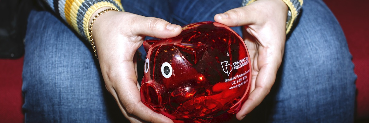 University of Portsmouth student holding red plastic UoP piggy bank