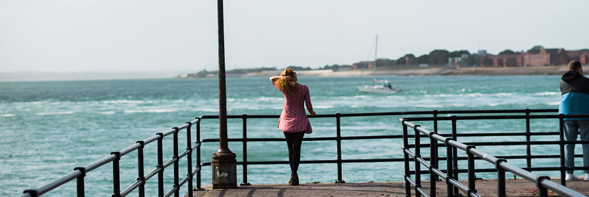 Student standing by a lamppost at the Pier, enjoying the sea view
