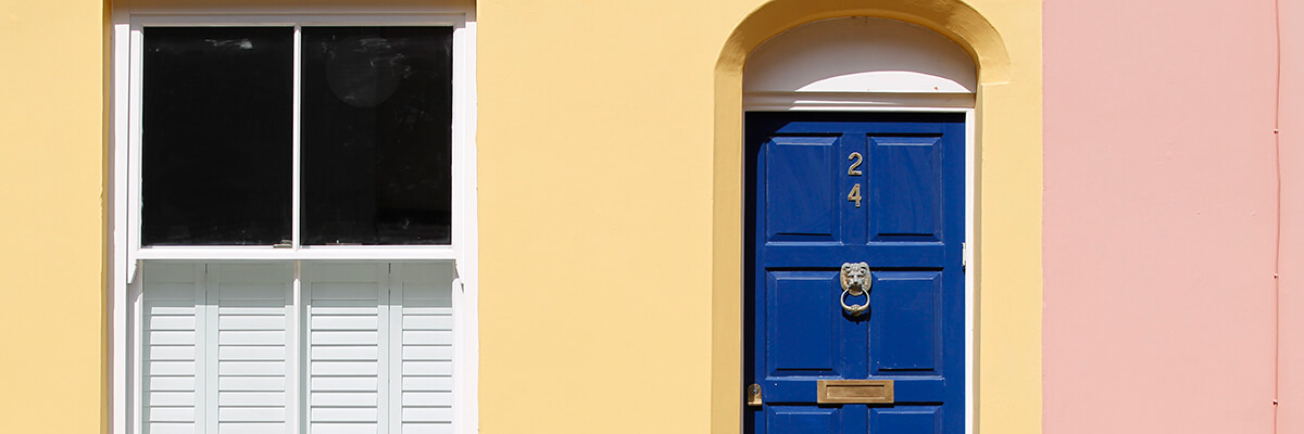 Red and yellow fascia of a terraced house, with dark blue door