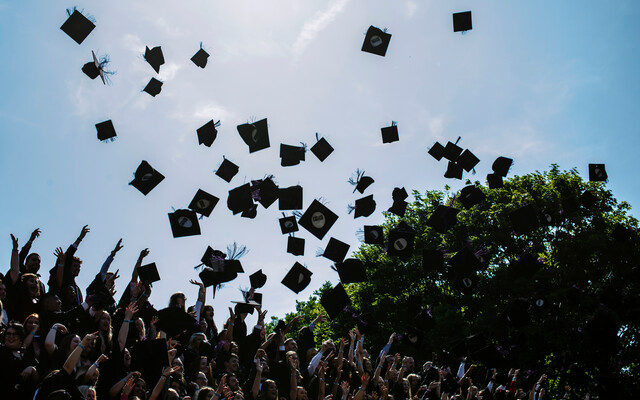 University of Portsmouth graduates celebrate by throwing mortarboards in the air
