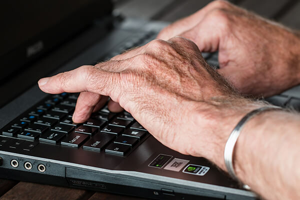 A pair of hands typing on a laptop keyboard