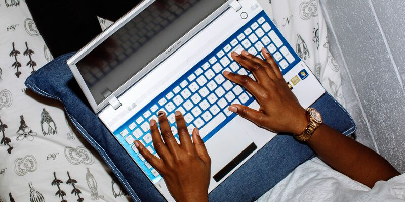 Two hands typing on a laptop.
