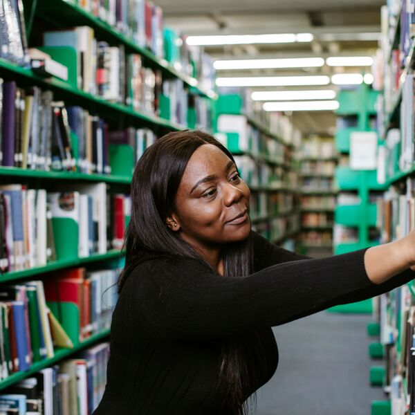 Female student reaches for book in library
